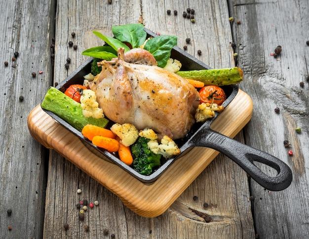 木製の背景に、ベーコンとスパイスと野菜とキジのグリル
