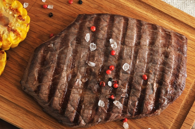 Grilled piece of beef with a crystalline salt, pepper and grilled corn