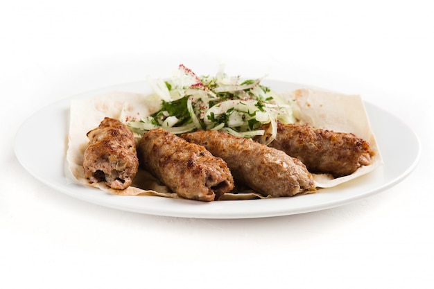 Grilled pieces of meat on a white plate with herbs and vegetables