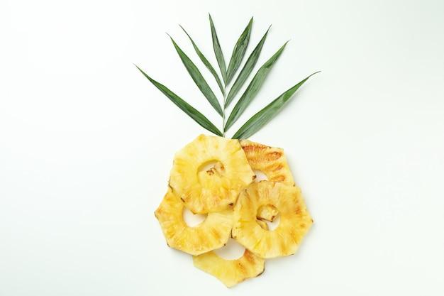 Ломтики и листья ананаса на гриле на белом фоне.