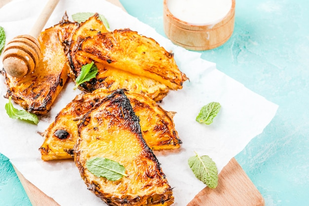 Grilled pineapple slices with mint honey and lime sauce on light blue background