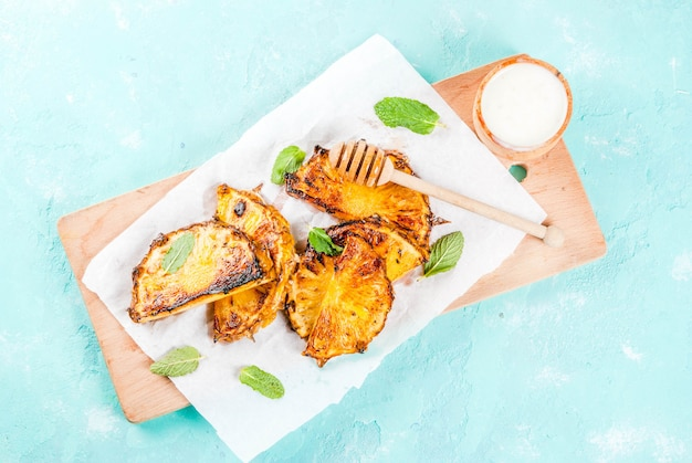 Grilled pineapple slices with mint, honey and lime sauce, on light blue   top view