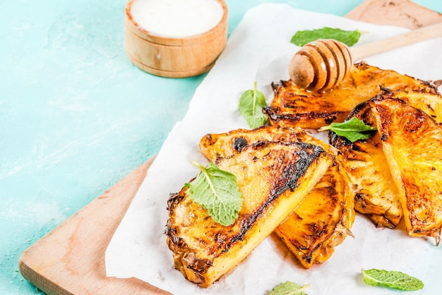 Grilled pineapple slices with mint, honey and lime sauce, on light blue
