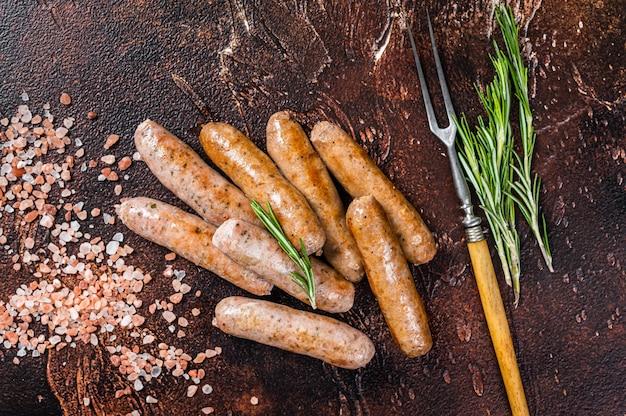 Жареные сосиски из свинины и говядины на кухонном столе. вид сверху.