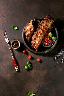 Grilled pork bbq ribs in ceramic plate served with meat fork, vegetable salad, cherry tomatoes, basil and barbeque sauce over dark brown texture background. top view, flat lay