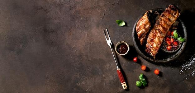 고기 포크, 절인 양파, 체리 토마토, 바질, 바비큐 소스와 함께 세라믹 접시에 구운 돼지 고기 바베큐 갈비. 어두운 갈색 질감 표면. 평면도, 평면 누워. 공간을 복사하십시오. 배너 크기