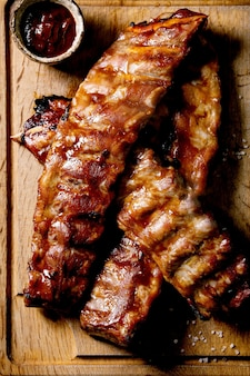 Grilled pork bbq ribs served barbeque sauce on wooden cutting board over dark background. top view, flat lay. close up