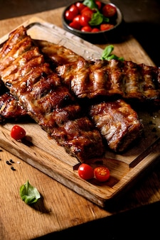 Grilled pork bbq ribs served with cherry tomatoes, basil and barbeque sauce on wooden cutting board over dark surface. close up