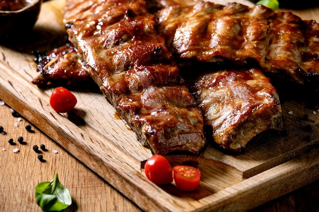 Grilled pork bbq ribs served with cherry tomatoes, basil and barbeque sauce on wooden cutting board on wood board. close up