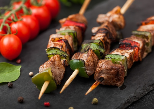 Grilled pork and chicken kebab with paprika on stone chopping board with salt, pepper and tomatoes on black.