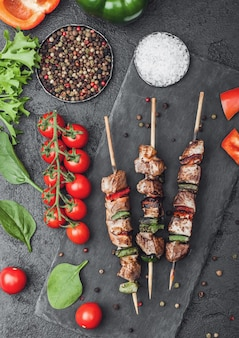 Grilled pork and chicken kebab with paprika on stone chopping board with salt, pepper and tomatoes on black