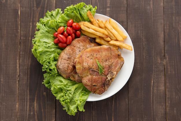 나무 배경에 감자 튀김과 구운 돼지 고기 스테이크와 야채