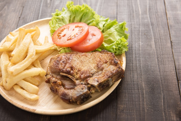 Grilled pork chop steak and vegetables with french fries on wooden table.