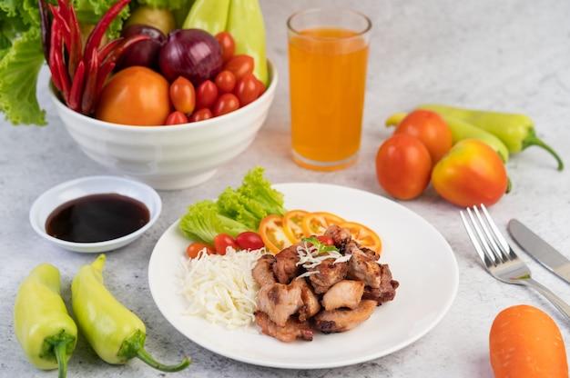 Жареная свиная котлета с помидорами и салатом, в белом блюде.