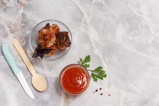 Свинина на гриле в стеклянной миске со свежей петрушкой и томатным соусом в стеклянной миске. барбекю, вид сверху.
