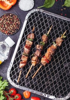 Grilled pork kebab with paprika on disposable coal bbq grill with fresh vegetables on black