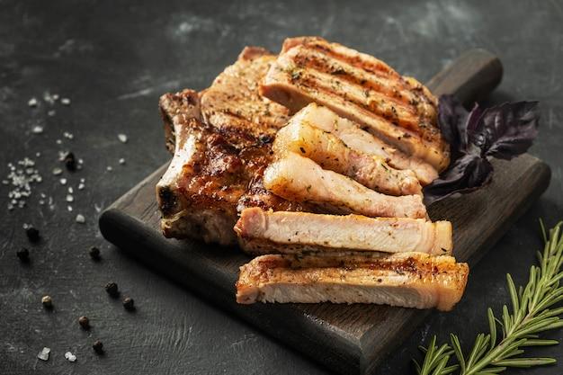 Жареная свиная корейка на деревянной доске на темной поверхности,