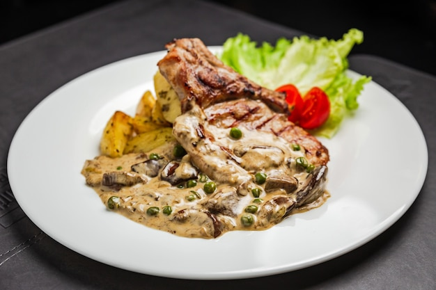 Grilled pork meat on the bone with mushroom sauce, green peas, potato and cherry tomato