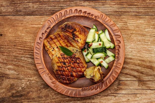 焼きにんにくときゅうりを添えた豚肉のグリル