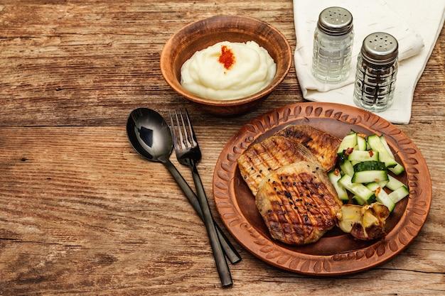 焼きにんにく、きゅうり、マッシュポテトを添えた豚肉のグリル