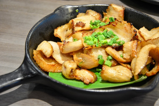 Grilled pork neck with sliced green onions on the top in black pan on wooden table background