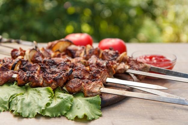 Свинина-гриль на металлических шпажках, обжаренная на гриле, и листья салата на деревянной разделочной доске с томатным соусом в миске и свежими помидорами на заднем плане. барбекю, пикник
