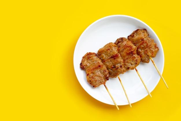 Свинина на гриле на белой тарелке на желтом фоне. вид сверху