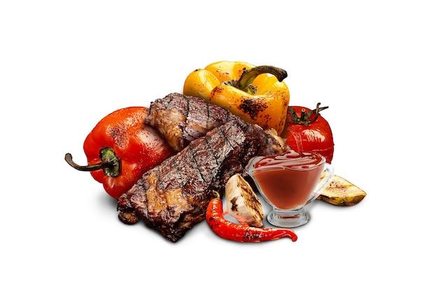 Стейки из свинины или говядины на гриле с красным и желтым болгарским перцем, кабачками, помидорами, перцем чили, половиной чеснока и красным соусом или кетчупом
