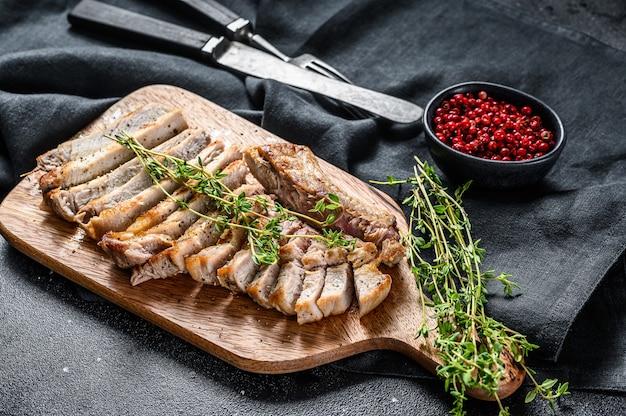 Grilled pork rib chop steak. organic meat. black background. top view.