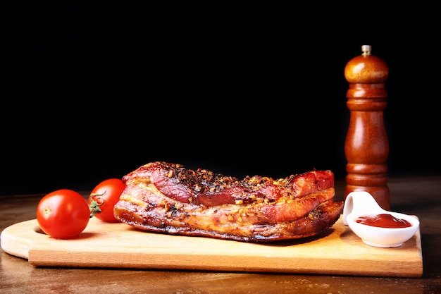 Grilled pork ribs barbecue striploin steak with sauce and tomatoes on cutting board.