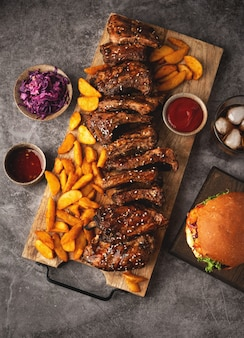 Grilled pork ribs and fried potato wedges on a wooden board, burger and cola glass, sause. top view, fast food.