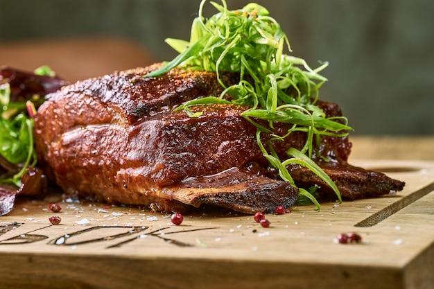 木の板にバーベキューソースで焼いたポークリブ。バーベキュー、アメリカ料理。クローズアップ、セレクティブフォーカス