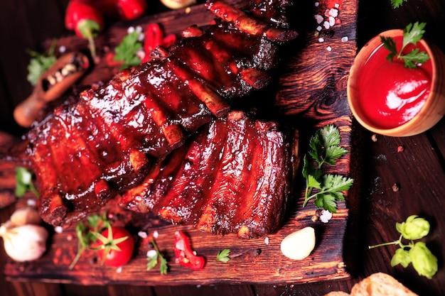 Свиные ребрышки на гриле со специями и овощами на деревянном фоне Premium Фотографии