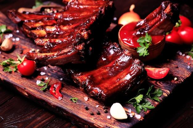Свиные ребрышки на гриле со специями и овощами на деревянном фоне
