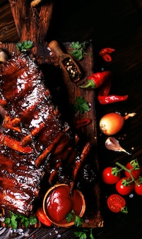 Grilled pork ribs with spices and vegetables on a wooden background