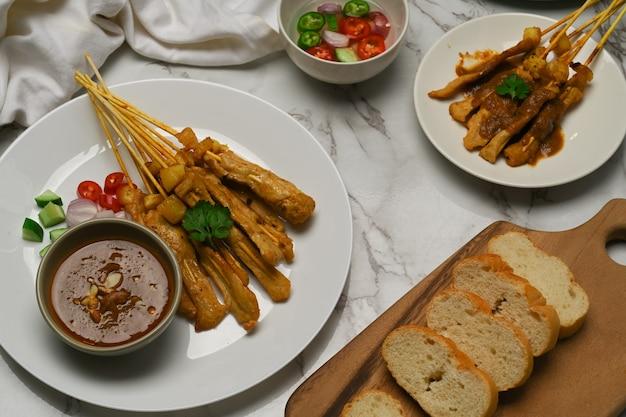 오이와 양파를 곁들인 구운 돼지 고기 사테이 (moo satay), 땅콩 소스와 구운 빵 제공
