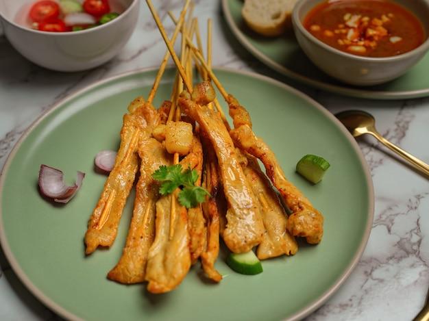 오이와 양파를 곁들인 구운 돼지 고기 사테이 (moo satay), 땅콩 소스와 반찬 제공