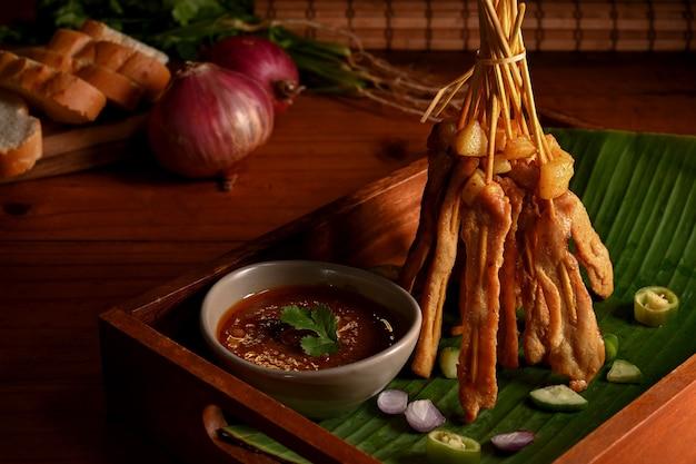 오이와 양파를 곁들인 구운 돼지 고기 사테이 (moo satay) 나무 테이블에 땅콩 소스와 함께 제공