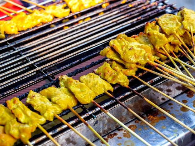 豚肉のグリルサテをストーブで焼きます。バーベキューポークローストグリルまたはサテローストポークの列、タイスタイルの屋台の食べ物。