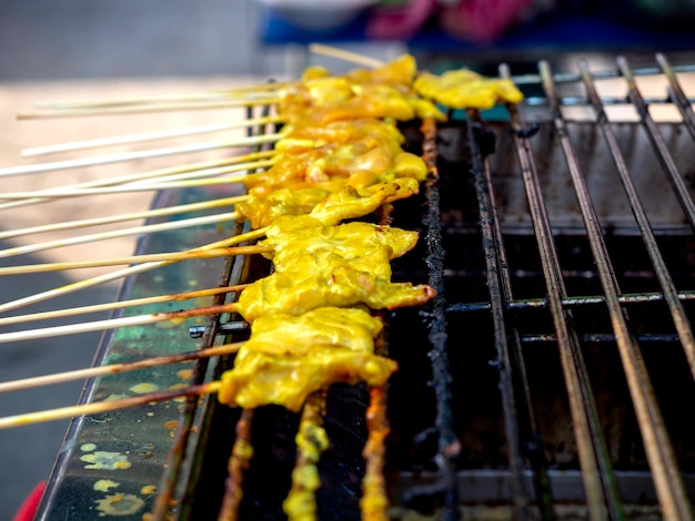 Grilled pork satays grilling on stove. row of barbecue pork roast grill or satay roast pork
