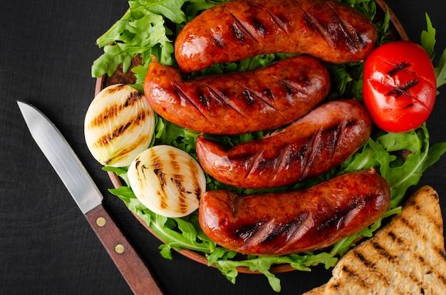Grilled pork sausages with arugula and vegetables on black background. close up, overhaed shot.