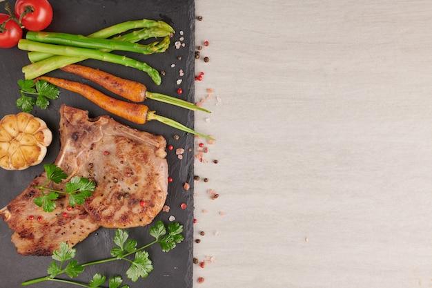 夏のバーベキューで焼いたポークステーキに、野菜、アスパラガス、にんじん、フレッシュトマト、スパイスを添えて。石の表面の黒いスレートのグリルステーキ。上面図。