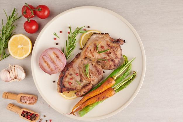 夏のバーベキューで焼いたポークステーキに、野菜、アスパラガス、にんじん、フレッシュトマト、スパイスを添えて。石の表面の白いプレートにグリルステーキ。上面図。
