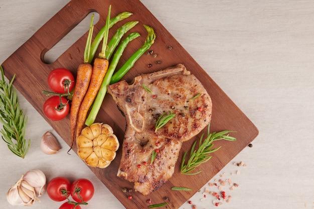 夏のバーベキューで焼いたポークステーキに、野菜、アスパラガス、にんじん、フレッシュトマト、スパイスを添えて。石の表面の木製まな板のグリルステーキ。上面図。