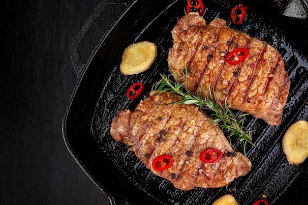 ローズマリー、唐辛子唐辛子、生姜の木の板のグリル鍋でポークのグリルステーキ。上面図。コピースペース。
