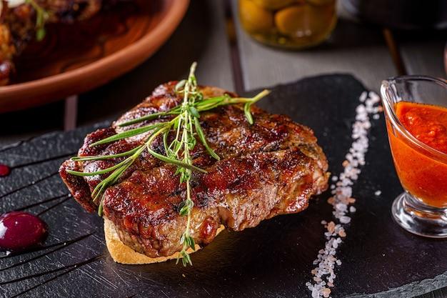 Grilled pork steak, lies on a piece of white bread