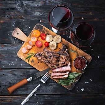 まな板で焼いたポークステーキ、美味しい肉片、赤ワイン1杯。二人で夕食。ナイフとフォーク