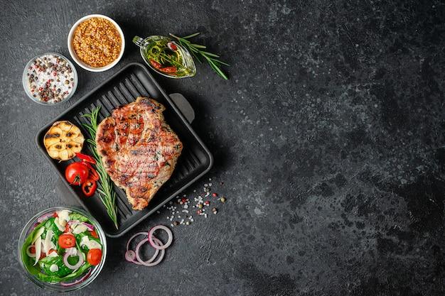 暗い背景にスパイスと野菜を添えた鋳鉄鍋で焼いたポークステーキ