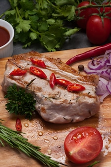 Grilled pork steak with red onion, carrot and tomato sauce