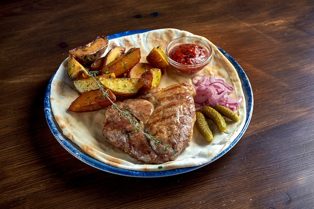 Grilled pork steak with spices and potato garnish, served in a plate with pickled onions, cucumber and red sauce on a wooden surface